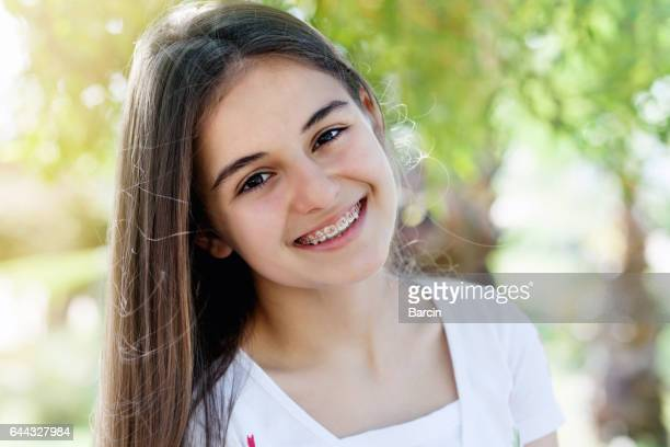 Pretty teenage girl wearing braces smiling cheerfully