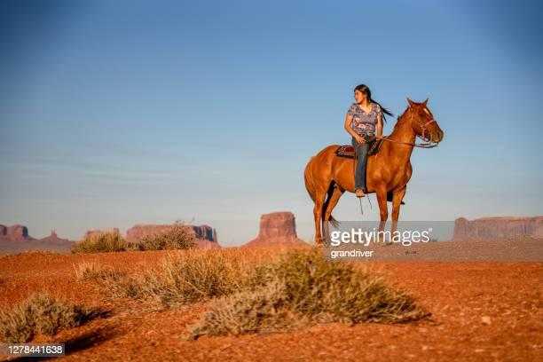 jolie adolescente navajo girl montant son cheval dans le désert du nord de l'arizona dans le parc tribal monument valley au crépuscule - apache photos et images de collection