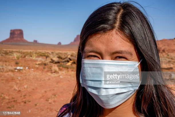 pretty teenage navajo native american girl in the northern arizona desert smiling through the covid-19 mask in a portrait with the buttes of the monument valley tribal park in the background flattening the curve and stopping the spread - cherokee indian women stock pictures, royalty-free photos & images