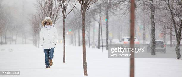 Pretty teenager girl in the white jacket under snowfall