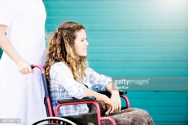 Pretty teenager in wheelchair pushed by obscured nurse smiles