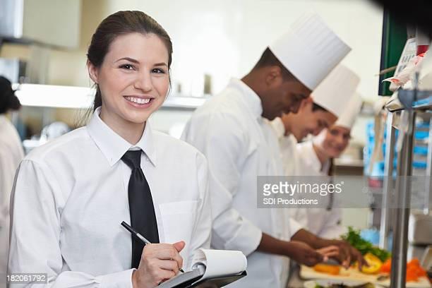Pretty waitress in restaurant kitchen with chefs preparing food