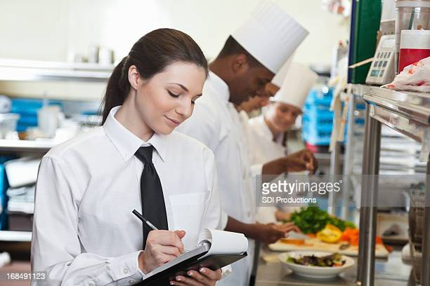 Pretty waitress looking at order in fancy restaurant kitchen