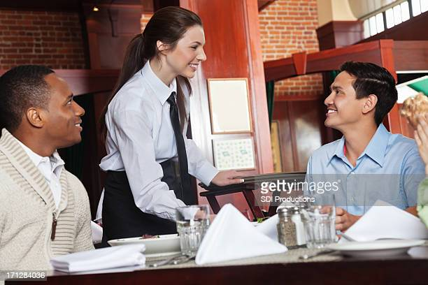 Pretty waitress talking with customers at table in nice restaurant