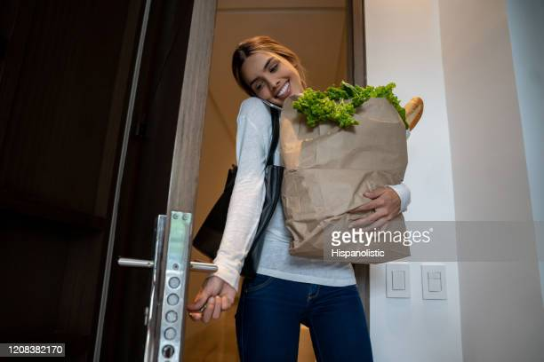pretty woman arriving home carrying groceries in a paper bag opening the door and on a phone call - entrar imagens e fotografias de stock