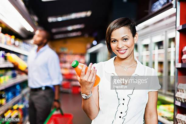 Pretty woman chooses orange juice in supermarket and smiles