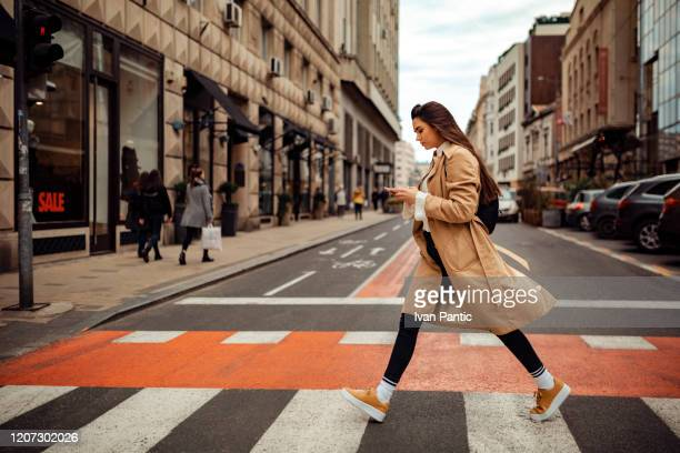 pretty woman crossing the street - street fashion stock pictures, royalty-free photos & images