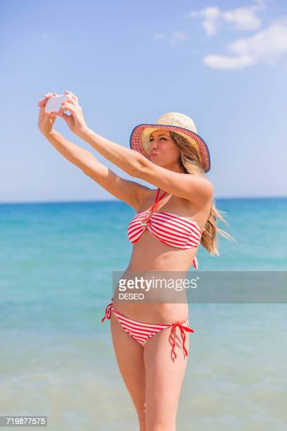 Pretty woman doing a selfie at the beach
