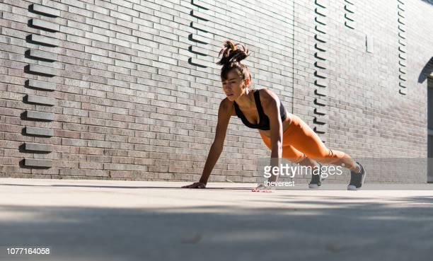a pretty woman doing push-ups on the street of new york - plank stock pictures, royalty-free photos & images