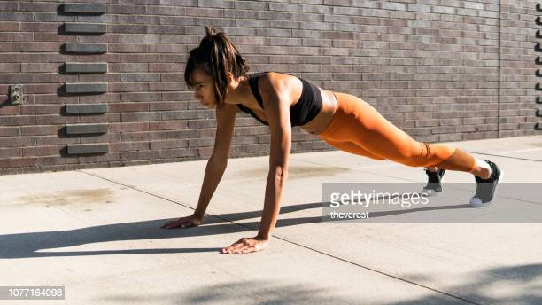 a pretty woman doing push-ups on the street of new york - plank position stock pictures, royalty-free photos & images