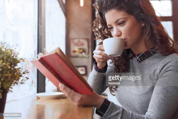 pretty woman enjoin coffee and reading book - leggere foto e immagini stock