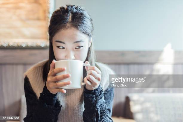 pretty woman enjoying a cup of cappuccino in cafe shop - 20 29 years stock pictures, royalty-free photos & images