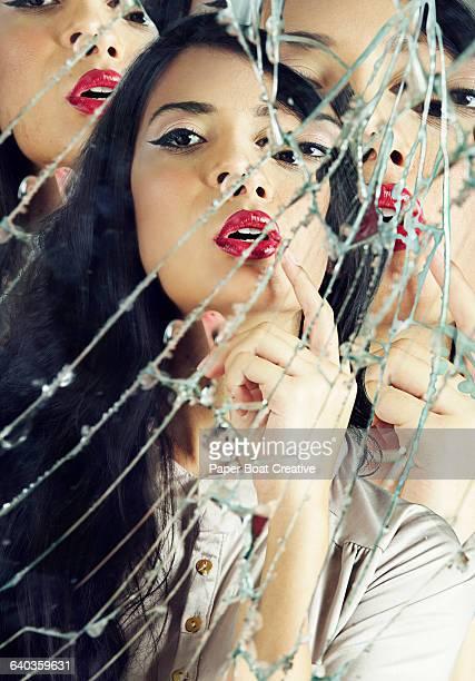 Pretty woman fixing her makeup in broken mirror