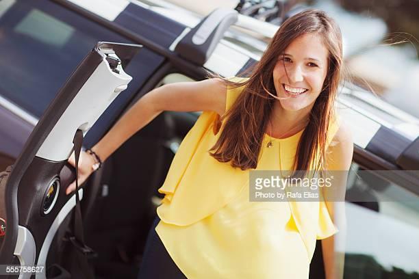 pretty woman getting out of car - gele trui fietstrui stockfoto's en -beelden