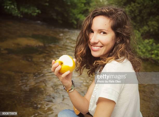 Pretty woman holding bitten apple by stream