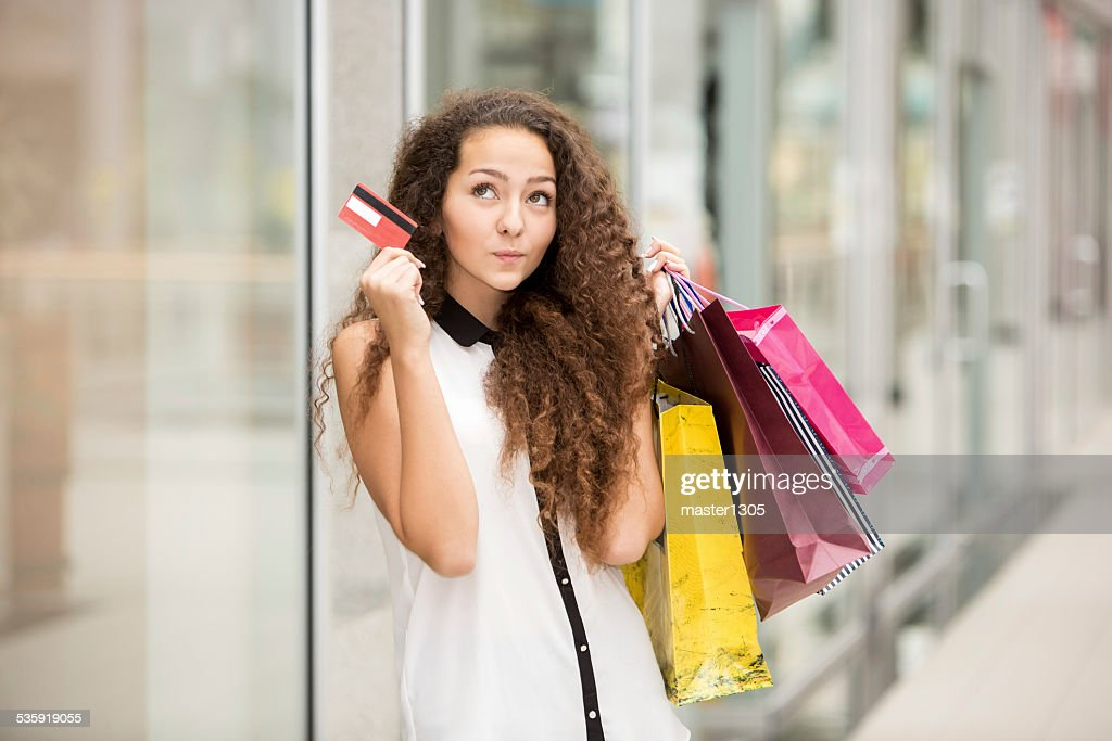 Pretty woman holding shopping bags and showing blank credit card : Stock Photo