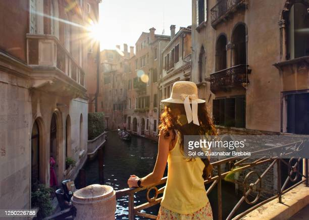 pretty woman in hat and yellow t-shirt seen from behind standing on a venice bridge looking at a narrow canal in the beautiful evening light - venice italy stock pictures, royalty-free photos & images