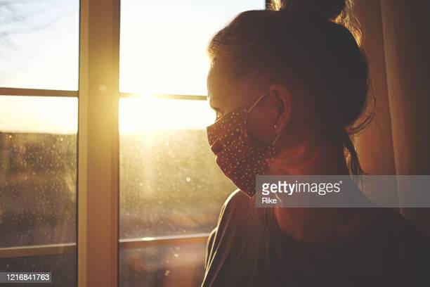 pretty woman in quarantine with mask, looks out the window - mental health stock pictures, royalty-free photos & images