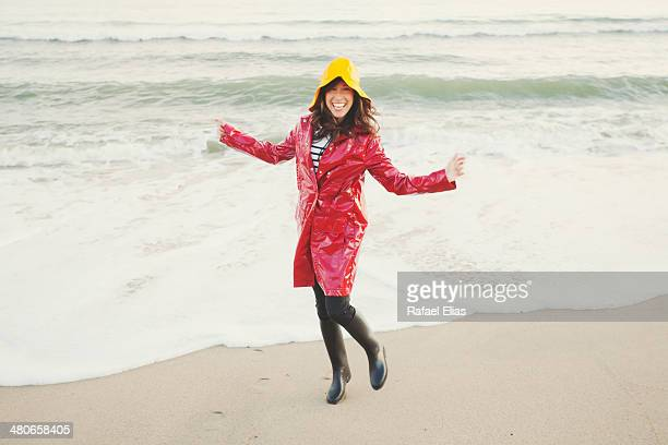pretty woman in rain clothes on the beach - gummistiefel frau stock-fotos und bilder