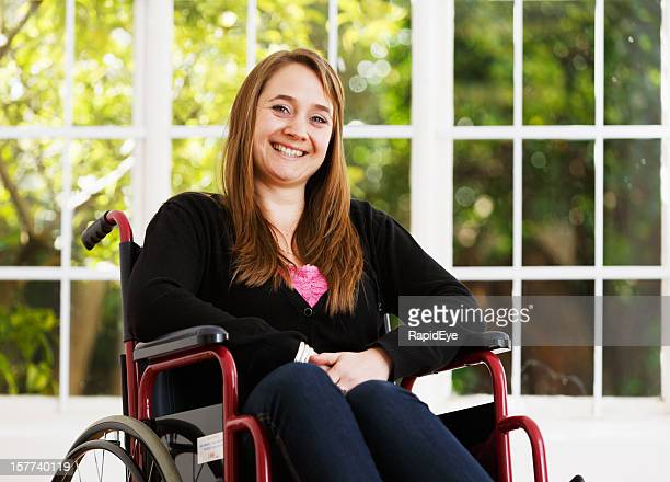 Pretty woman in wheelchair smiles bravely, overcoming adversity