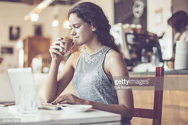Pretty woman is enjoying a cup of coffee
