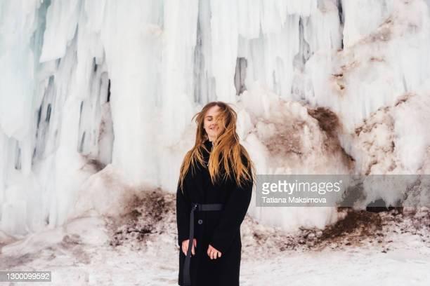 pretty woman jump in coat and ice waterfall, winter. - casaco - fotografias e filmes do acervo
