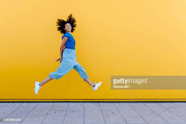 pretty woman jumping for joy in front of yellow wall - saltare foto e immagini stock