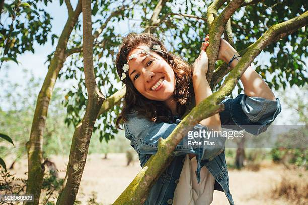 Pretty woman leaning on tree branches