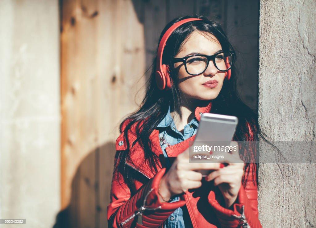 Mooie vrouw luisteren muziek met koptelefoon van een telefoon : Stockfoto