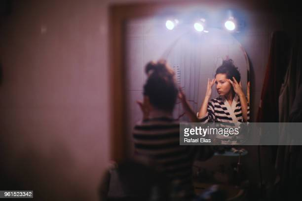 pretty woman looking at herself in the bathroom mirror - vanity mirror stock photos and pictures