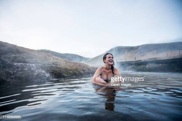 pretty woman lying on back in thermal water river. - lagoon stock pictures, royalty-free photos & images
