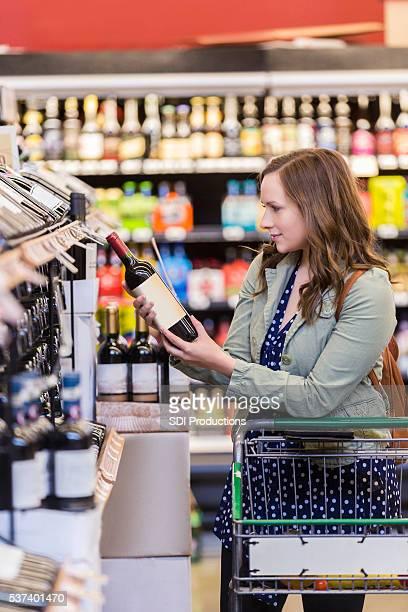 Bonita mulher escolher o vinho na loja