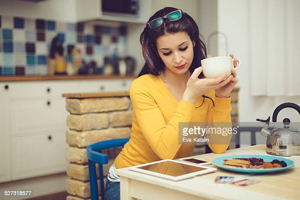 Pretty woman reading tablet and having breakfast in the kitchen