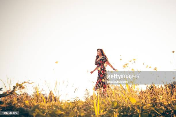 Pretty woman running through field of wildflowers
