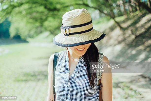 pretty woman shielding face with straw hat smiling - yiu yu hoi stock pictures, royalty-free photos & images