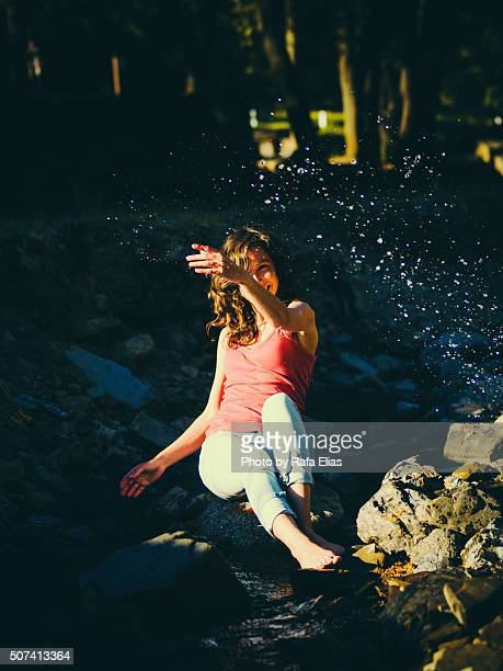 pretty woman sitting on rock in stream and splashing water - women in wet t shirts stock pictures, royalty-free photos & images