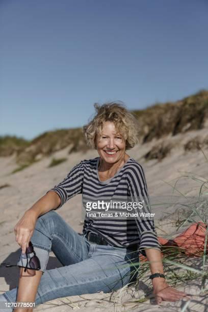 pretty woman sitting on the beach and enjoying the sun. - aktiver lebensstil stock-fotos und bilder