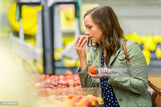 Pretty woman smelling fresh fruit