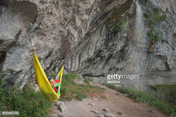 Pretty woman smiling at camera while relaxing in yellow hammock