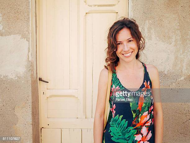 pretty woman smiling next to wooden door - iberian stock photos and pictures