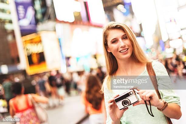 La hermosa mujer sonriente con cámara en times square