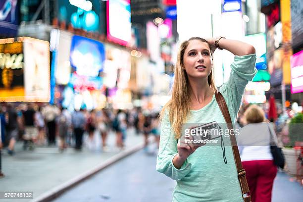 pretty woman smiling on times square with camera