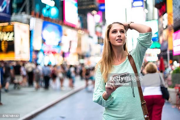 Bonita mulher sorridente no times square com câmara
