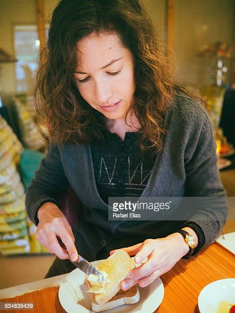 pretty woman spreading butter on bread - margarine stock pictures, royalty-free photos & images