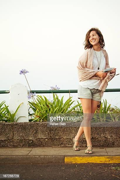 Pretty woman standing on sidewalk
