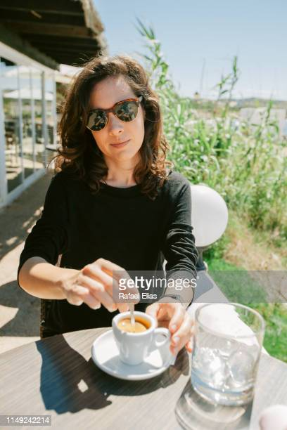 pretty woman stirring coffee in the terrace bar - reed grass family stock photos and pictures