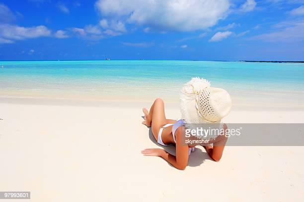 美しい女性のビーチでの日光浴をお楽しみください。
