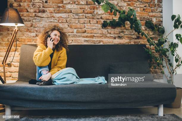 pretty woman talking on the phone - sofa stock pictures, royalty-free photos & images