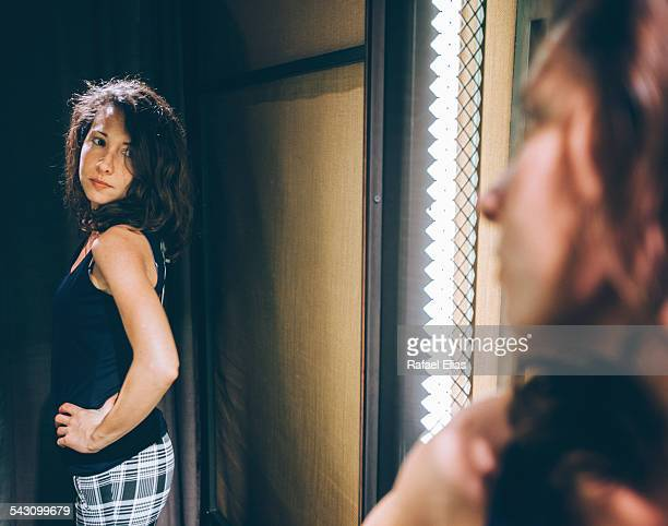 pretty woman trying on clothes in changing room - full length mirror stock photos and pictures