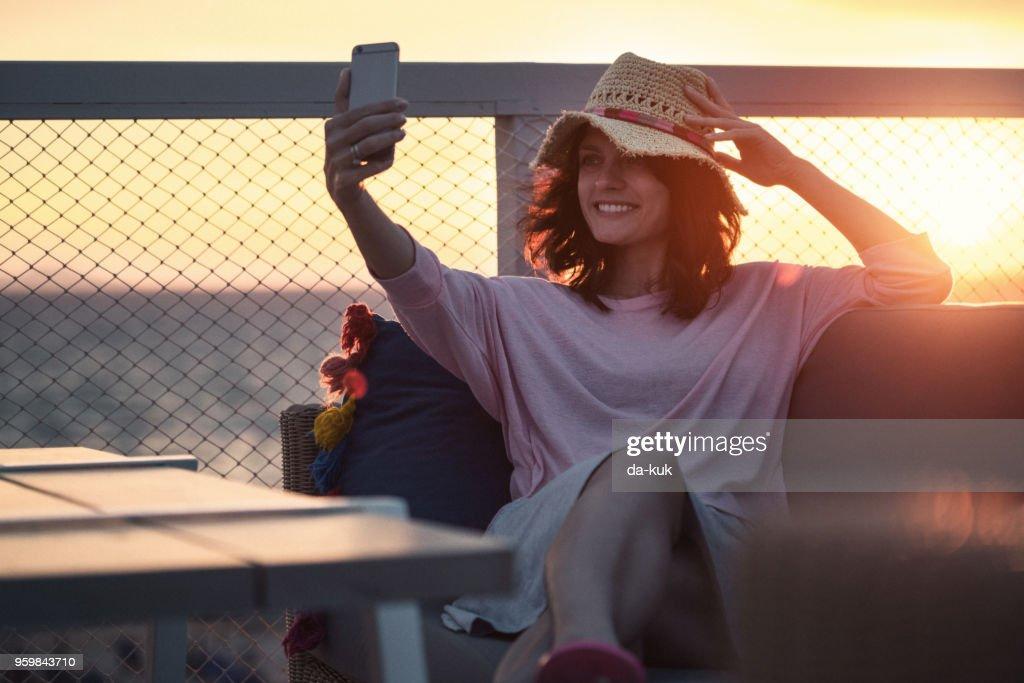 Hübsche Frau mit Smartphone im Urlaub bei Sonnenuntergang : Stock-Foto